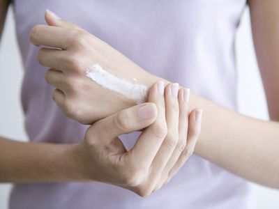 Woman applying cream to hands, close-up