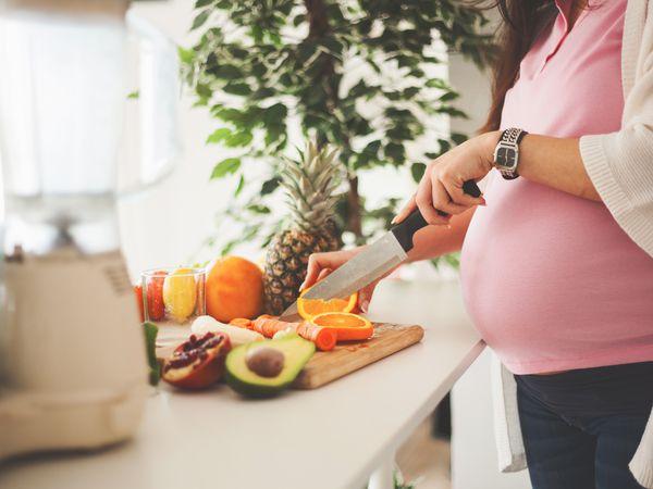 Pregnant woman chopping fresh produce
