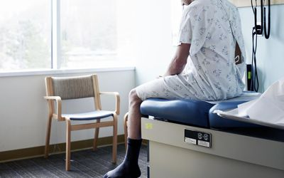 Male patient in gown waiting on exam table