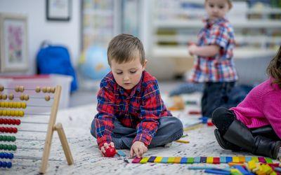 Small boy lining up blocks at preschool
