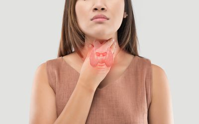a woman holding her thyroid