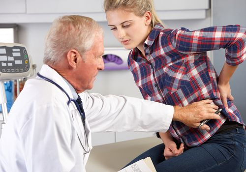 Teenage girl at the doctor with back pain