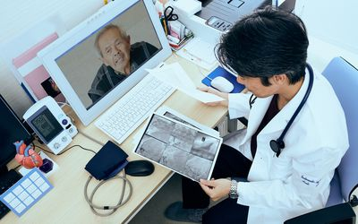 Doctor on a telehealth consultation with an older male patient