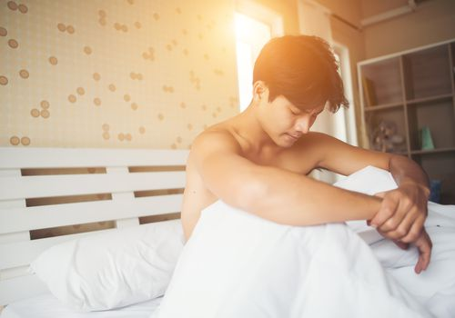 Man sitting in bed worried and shirtless