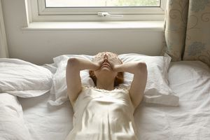 woman on bed with hands over eyes