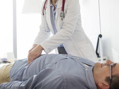 Doctor examining man's stomach