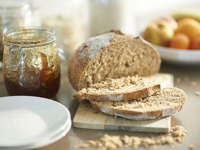 Sliced wheat bread and strawberry jam jar