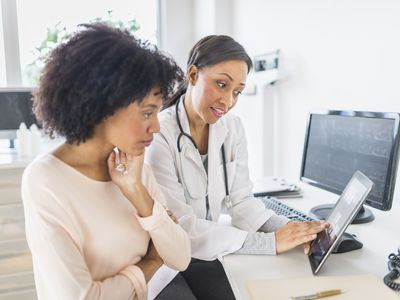 Female patient and female doctor talking, looking at screen.
