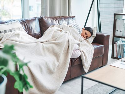 A young woman is resting on a dark brown leather couch with an ivory colored blanket covering her.