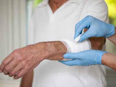 Nurse changing surgical bandage on patient