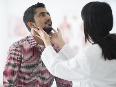 A doctor checking a man's lymph nodes