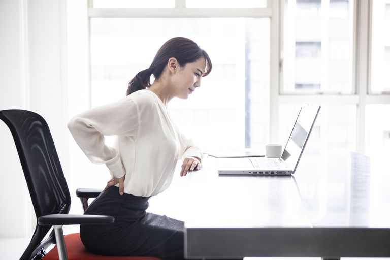 Woman sitting at her desk rubbing her back