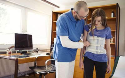 A physical therapist and a young girl in a scoliosis brace.