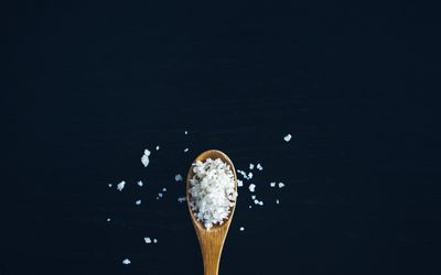 Flaky salt on a brown wooden spoon on a black background.