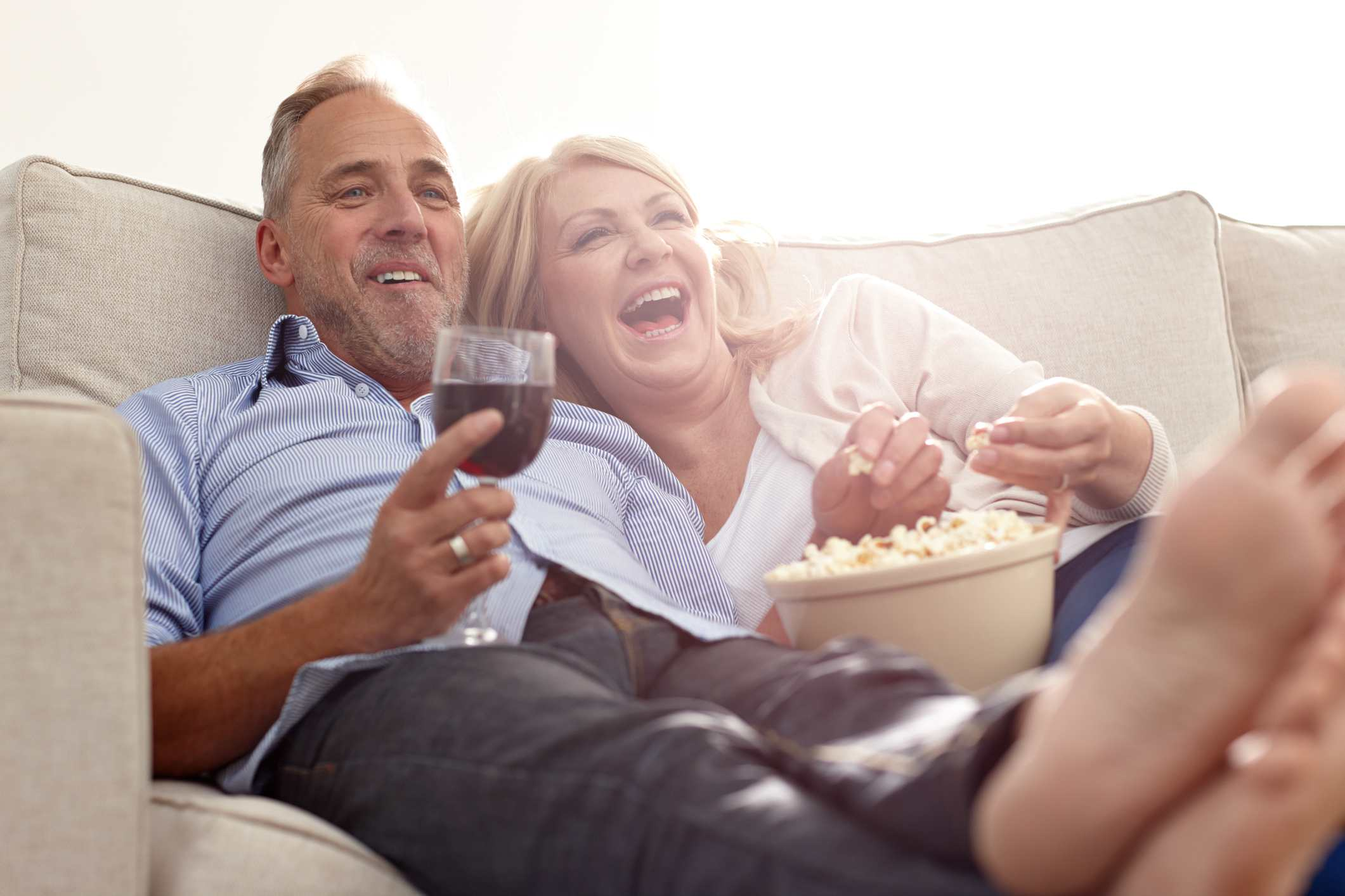 Mature couple drinking wine on couch