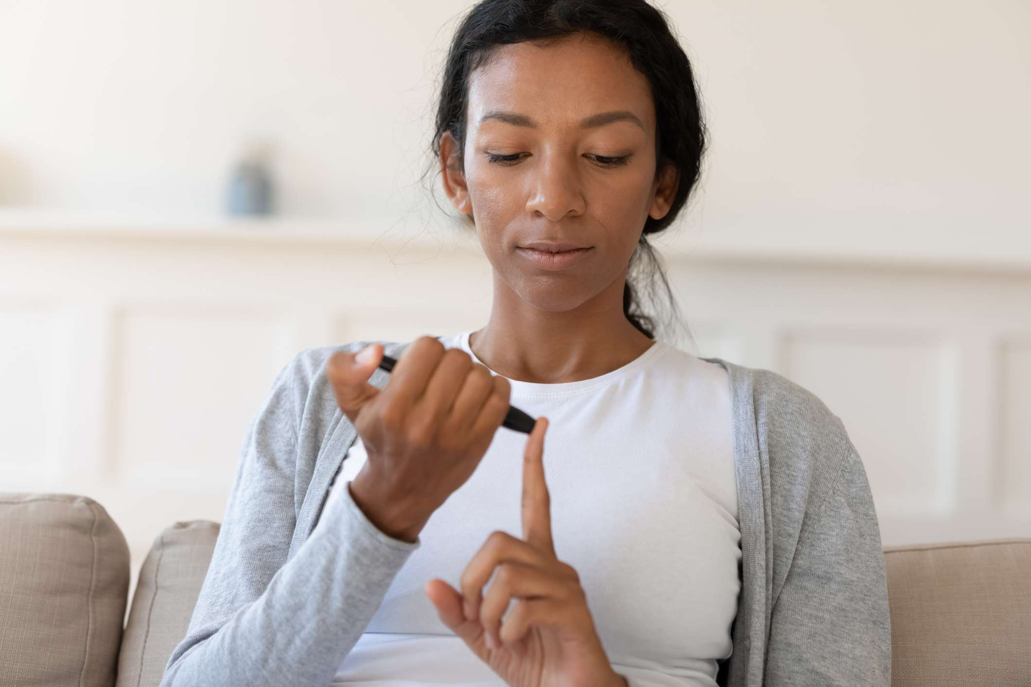 Woman who is hyperglycemic pricking her finger for a blood test.