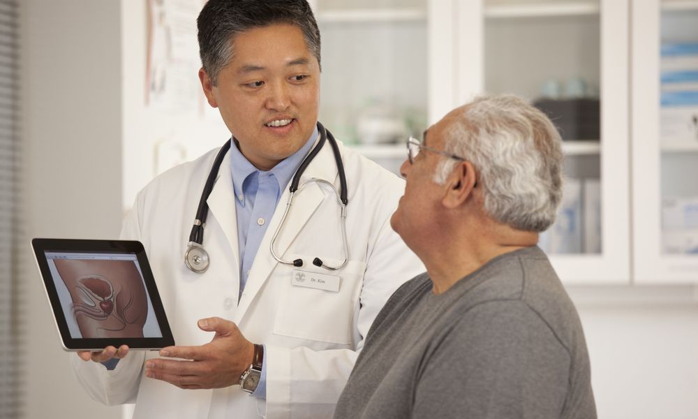 Doctor using digital tablet to talk to senior man - stock photo