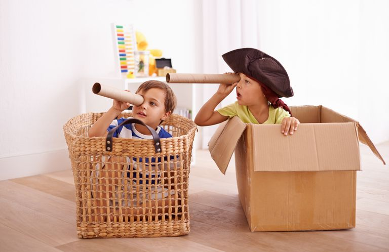 Photo of two kids, one sitting in a basket and one sitting in a box, pretending to be pirates and looking through empty paper towel rolls