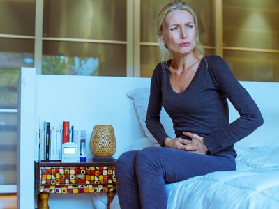 A woman sitting on her bed in stomach pain