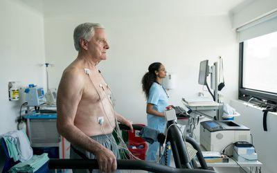 Senior man on a treadmill doing a stress test at the hospital while black nurse looks at the cardiac monitor