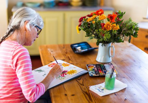Older adult woman painting flowers in a vase.