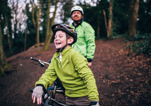 Happy smiling boy on a bicycle ride with his Father