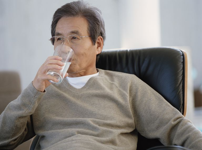 Senior man sitting on armchair drinking glass of water