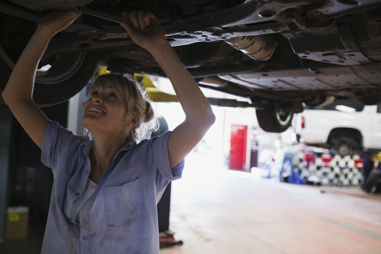 Photo of a woman mechanic working on a car.