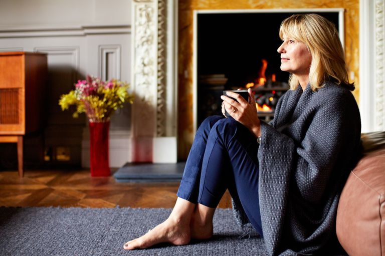 Shot of a mature woman relaxing on her living room sofa with a fire glowing in the background