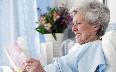 Senior woman reading card in hospital