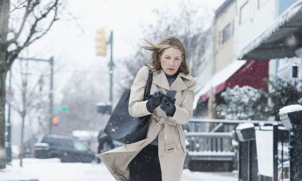Woman walking on snowy street