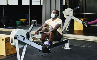 Man exercising at the gym wearing a face mask.