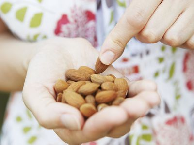 Close up of a white female hand filled with almonds.