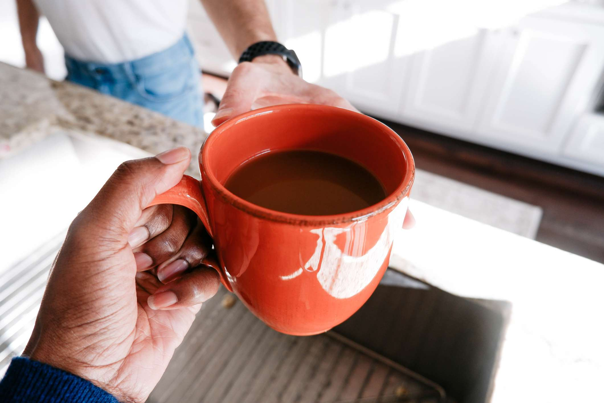 A man hands another man a cup of coffee.