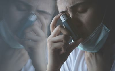 Adult using asthma inhaler while wearing a face mask to prevent COVID-19