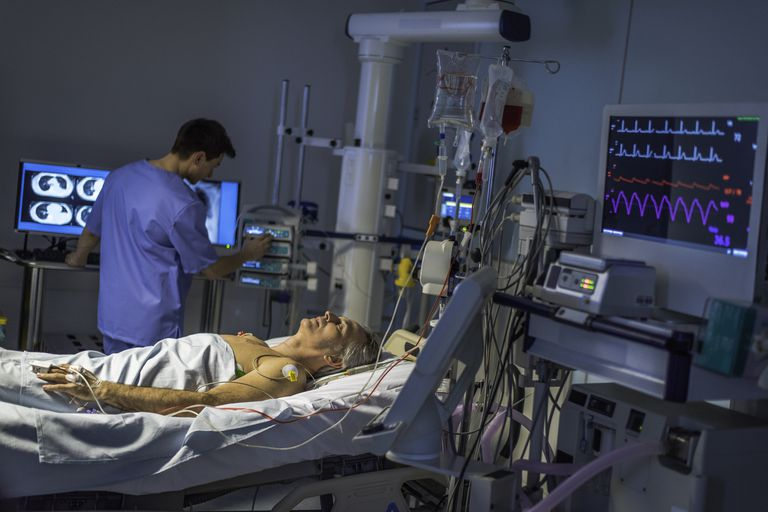 A doctor monitoring a patient in ICU