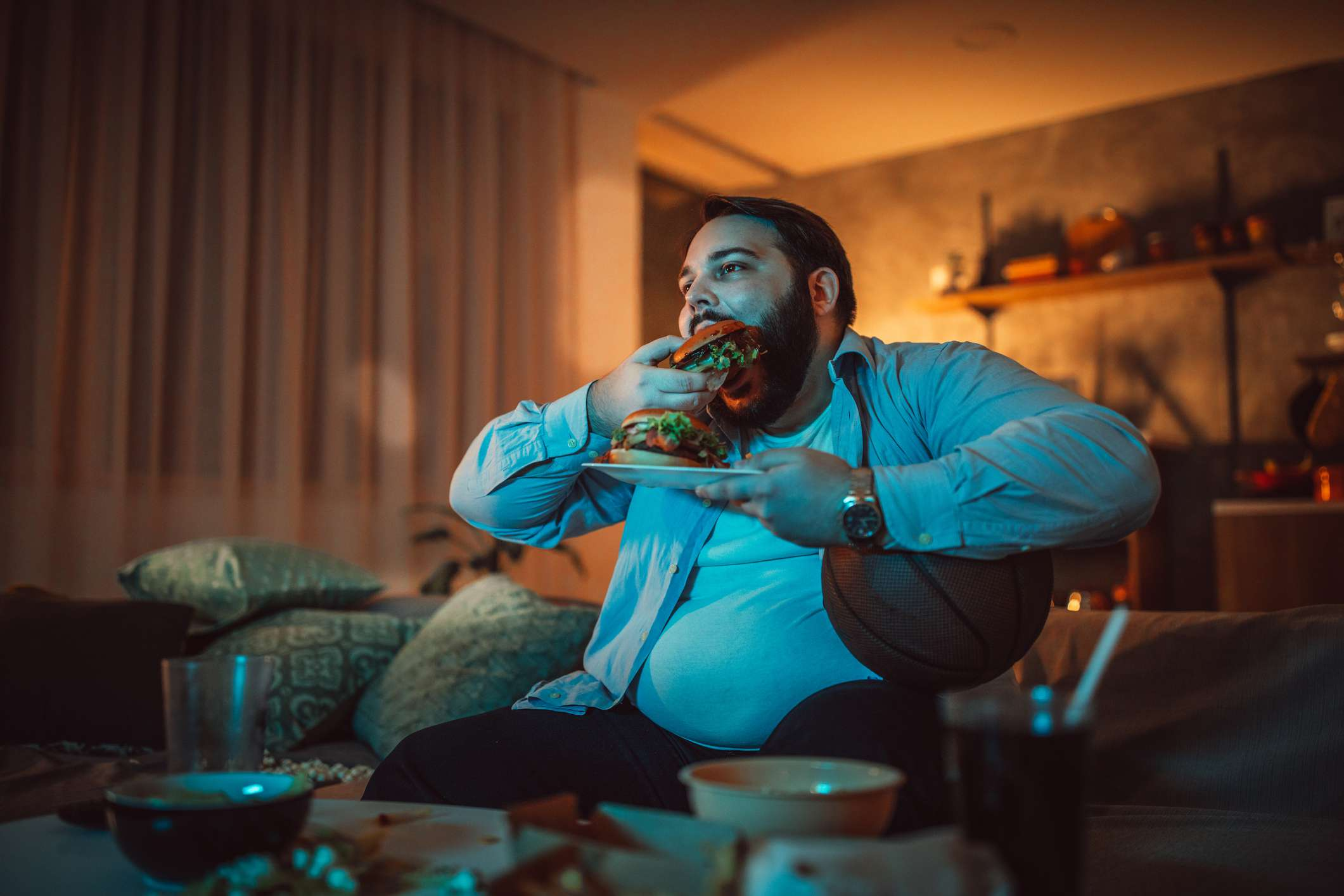 man sitting at home, eating burgers, and watching a sports match alone