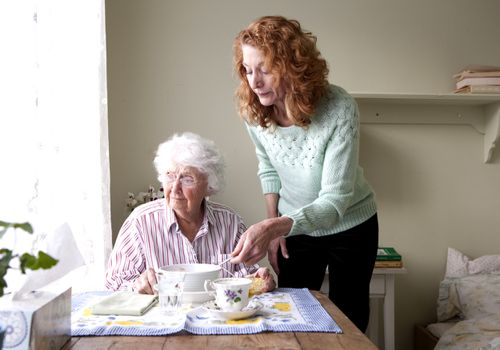 Woman feeding elderly woman