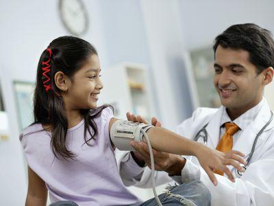 Doctor taking girl's blood pressure