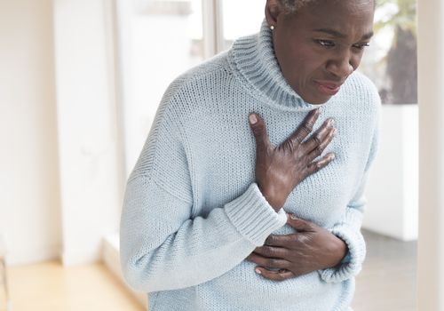 Woman touching chest in pain - stock photo
