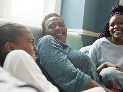 A grandmother sits on the couch with two young women. They all laugh.