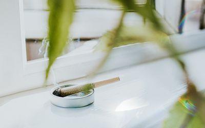 Smoking marijuana cigarette in a small metal ashtray sitting by an open window