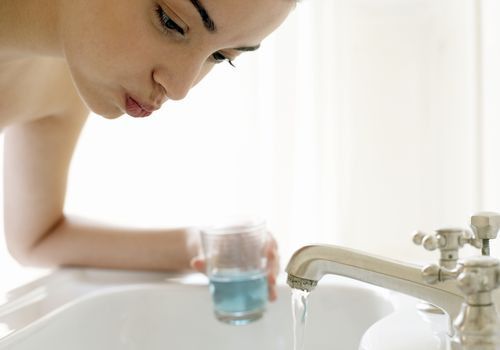 Young woman rinsing mouth, leaning over sink