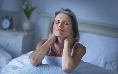 A woman in bed with neck pain