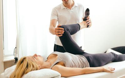Photo of PT examining a woman's knee.