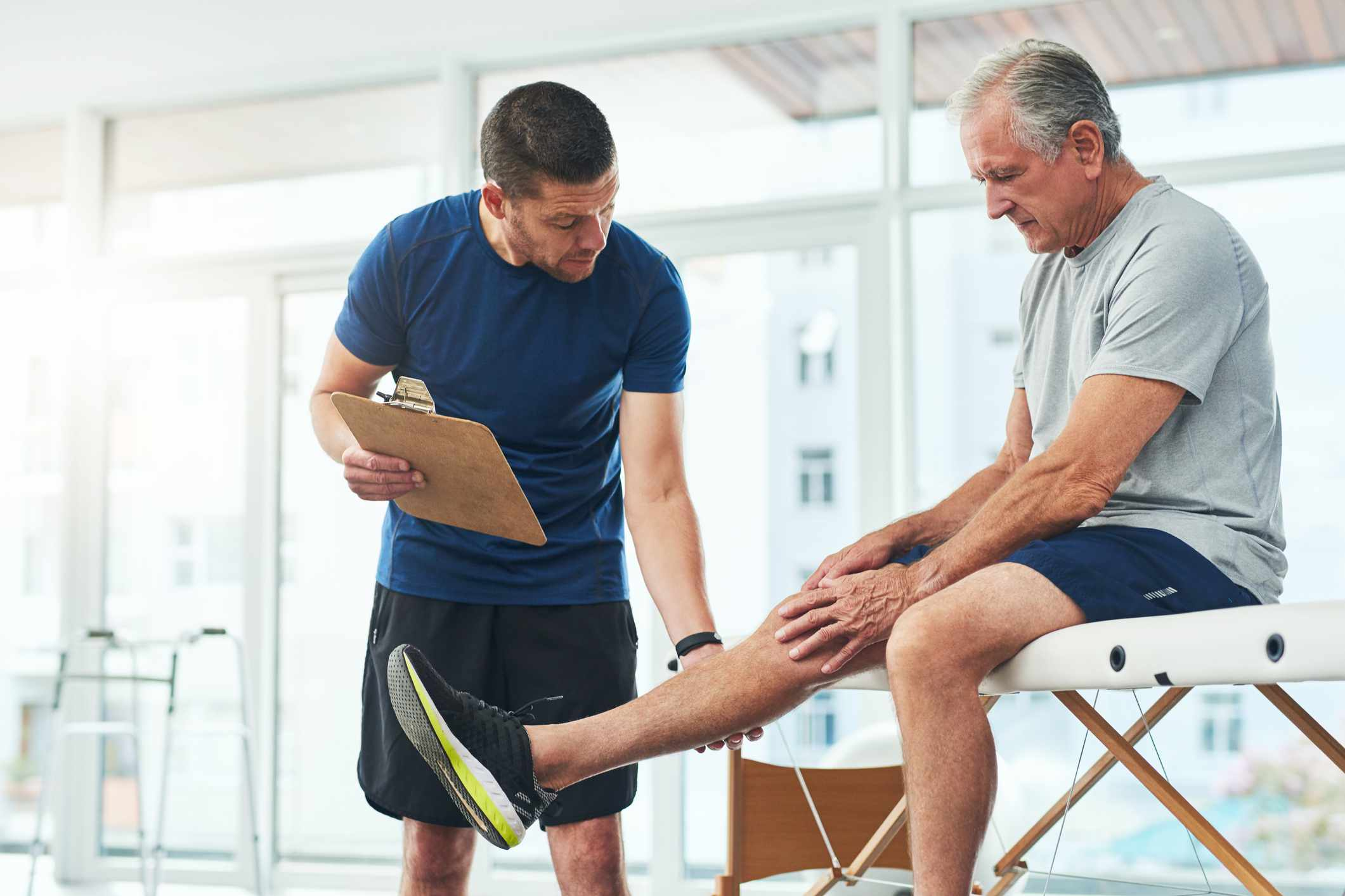 Man performing leg raise while physical therapist looks on