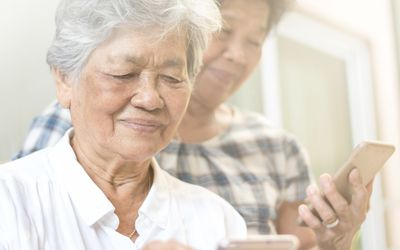 Older person uses smartphone but appears to have vision difficulties