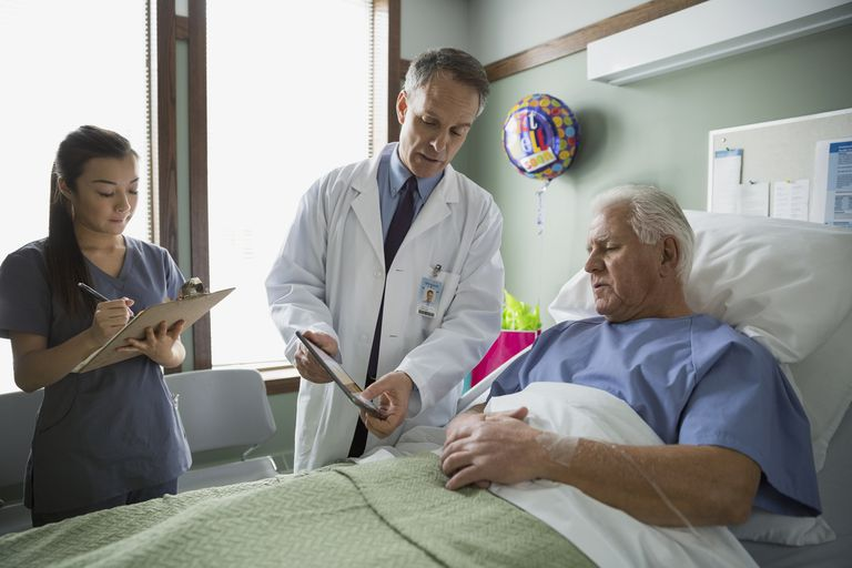Older man in hospital bed with doctor