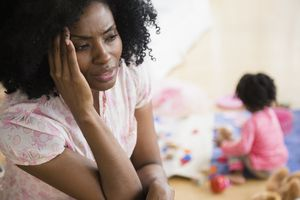 A Black mother appearing stressed, her young child is playing alone in the background.