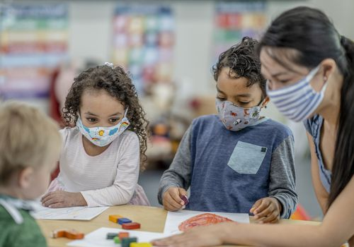Children wearing face masks at a child care center.